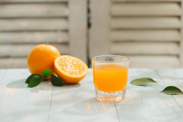 オレンジ ジュースとカット オレンジ テーブルの上