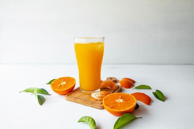 白い木製の背景にオレンジ ジュースと新鮮なオレンジ色の果物