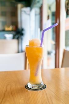 Orange juice blend smoothie glass in cafe restaurant