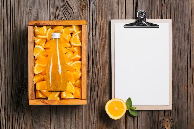 Orange juice bottle and clipboard on wooden background
