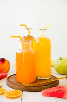 An orange juice bottles with drinking straw on wooden tray with fruits on wooden desk