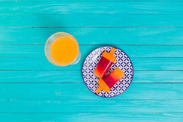 Orange juice and bright fruit popsicle on plate on wooden surface