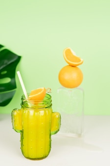 Orange juice in a cactus-shaped glass decorated with ice cube and orange. copy space.