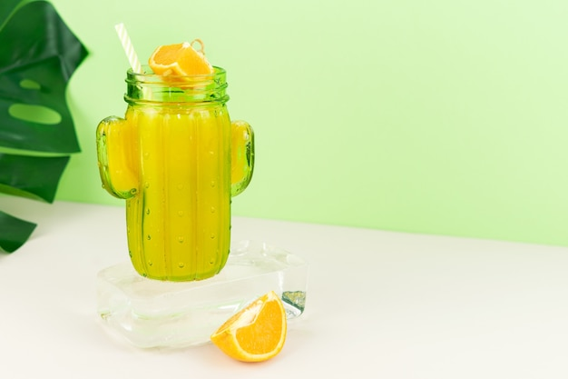 Orange juice in cactus shaped glass on ice block with fruit decoration. copy space.