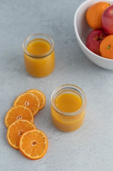 Orange juice in clear glass jar near sliced oranges and orange and apple fruits in round bowl