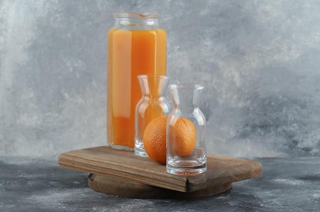 Arancia, succo di frutta e bicchieri vuoti su tavola di legno.