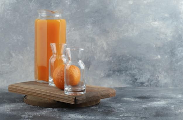 Arancia, succo e bicchieri vuoti su tavola di legno.