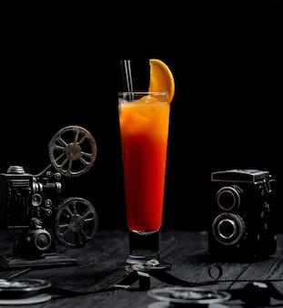 Succo d'arancia in un bicchiere allungato con una fetta d'arancia