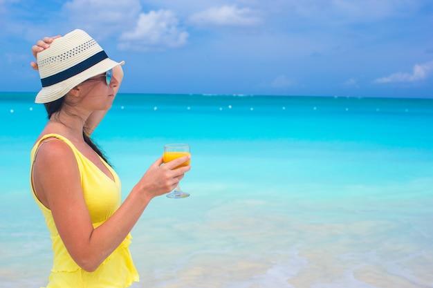 Orange juice in female hand on background of the sea