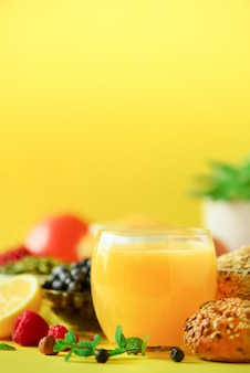 Orange juice, fresh berries, milk, yogurt, boiled egg, nuts, fruits, banana, peach for breakfast. healthy food concept.