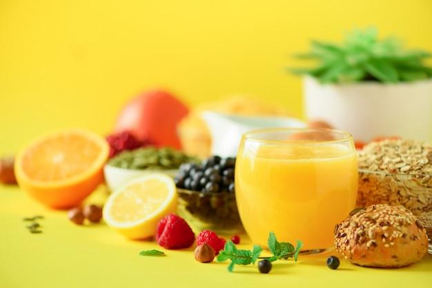 Orange juice, fresh berries, milk, yogurt, boiled egg, nuts, fruits, banana, peach for breakfast on yellow background.