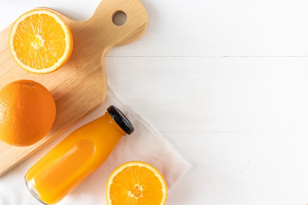 Orange juice in glass bottle with sliced fruit on white wood, top view and flay lay of natural source of vitamin c
