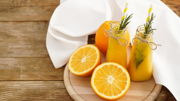 Orange juice in glass bottles decorated with a sprig of rosemary