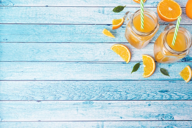Orange juice in glass jars and fresh oranges on a blue background.