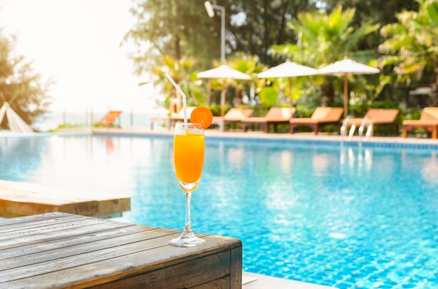 Orange juice glass on wooden table with swimming pool view background