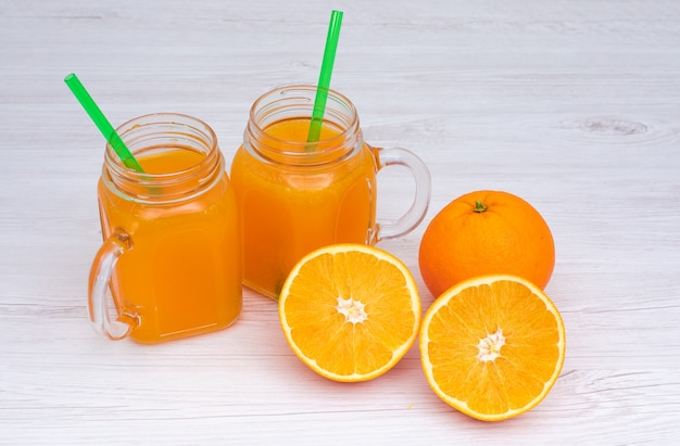 Orange juice in glasses and orange fruits on white surface