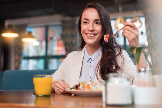 オレンジジュース。サラダを食べたり、カフェで昼食をとりながらフォークを運ぶ格好良い魅力的なエネルギッシュな女性