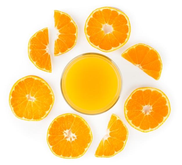 Апельсиновый сок в стеклянной чашке и кусочки выложены изолированными
