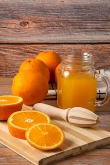 Апельсиновый сок в стеклянной банке на разделочной доске