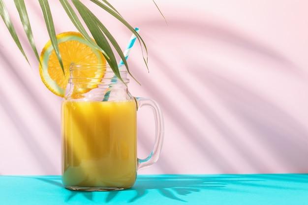 コピースペースと色の背景にガラスのオレンジジュース