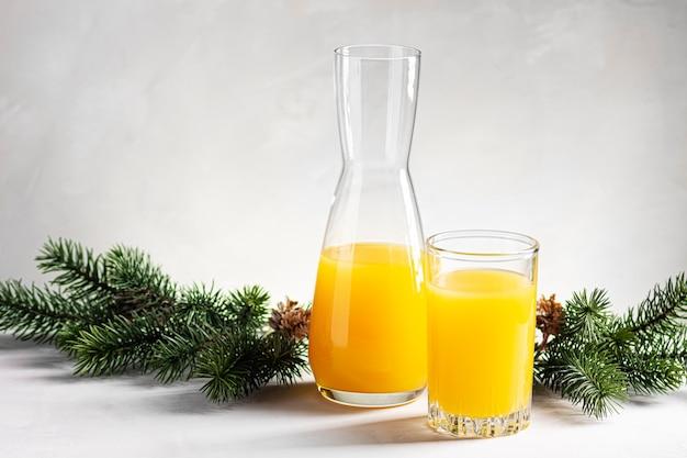 Апельсиновый сок в стакане стоит рядом с графином на фоне еловых веток