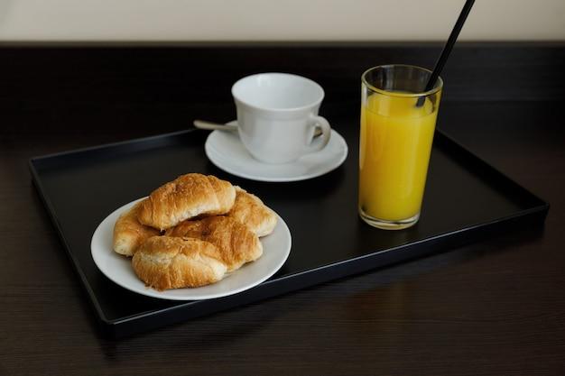 Апельсиновый сок в стакане с круассанами. завтрак в отеле, дома. чашка и блюдце белые. стол темно-коричневый. утро