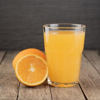木製のテーブルの上にフルーツとグラスのオレンジジュース。