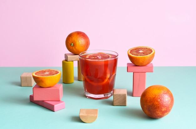Апельсиновый сок в стакане с подимами геометрических фигур и апельсинами на них на мятном и розовом фоне
