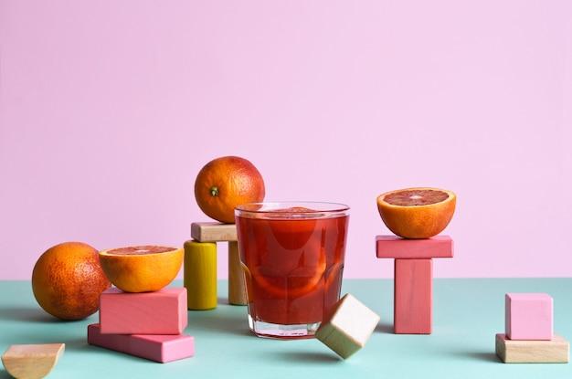 ミントとピンクの背景に幾何学的な形のpodimsとオレンジのガラスのオレンジジュース