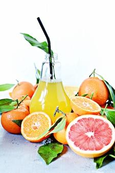 Апельсиновый сок в стакане с апельсинами, лимонами, грейпфрутами, мандаринами, лаймами.