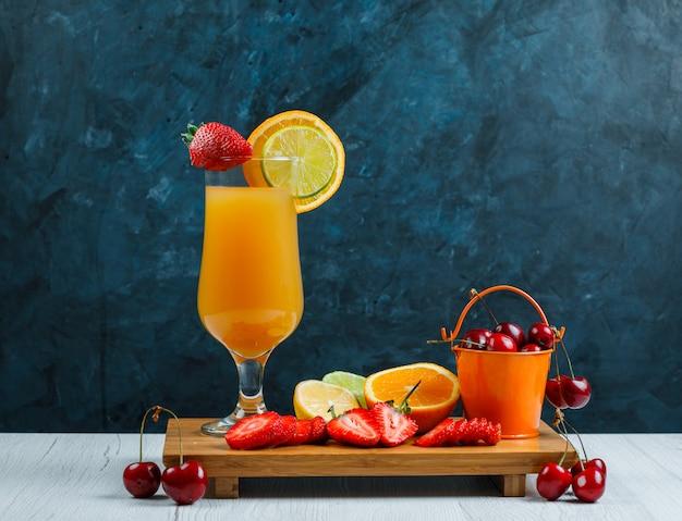 Апельсиновый сок в бокале с цитрусовыми, клубникой, вишней, разделочной доской на деревянном и шероховатом синем фоне
