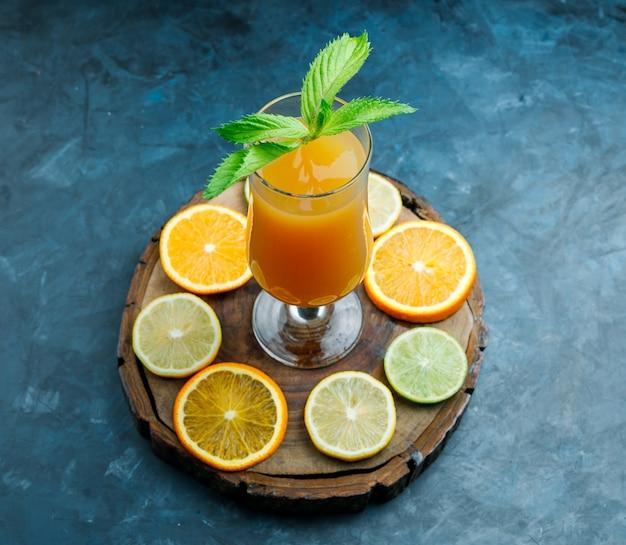 汚れた青と木の板にミント、ライム、レモン、オレンジのハイアングルとゴブレットのオレンジジュース