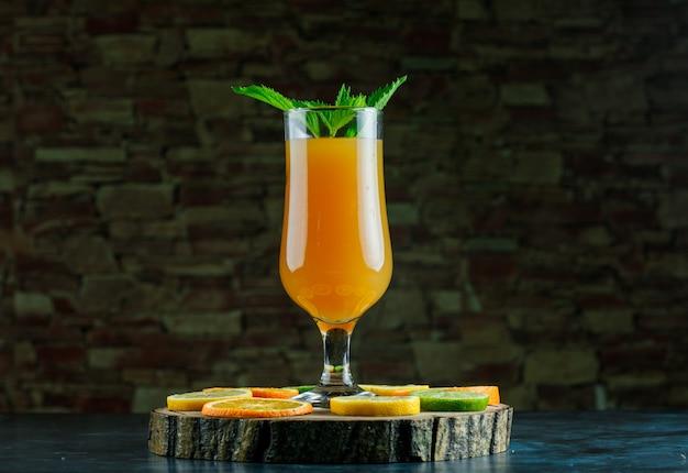 青とレンガの石の背景にミント、ライム、レモン、オレンジ、木の板の側面図とゴブレットのオレンジジュース