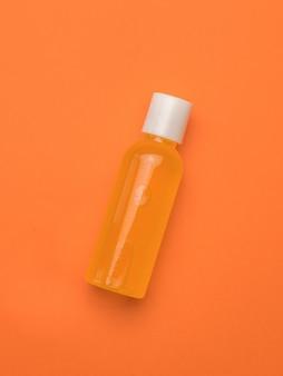 오렌지 배경에 플라스틱 병에 오렌지 주스. 미니멀리즘.