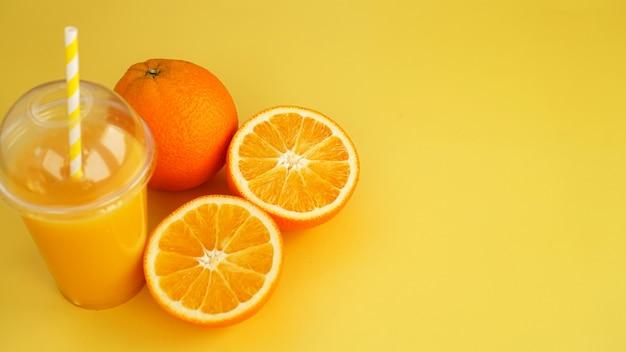 빨대로 플라스틱 유리에 오렌지 주스. 노란색 바탕에 오렌지 슬라이스. 카페의 배너 및 메뉴 여름 사진