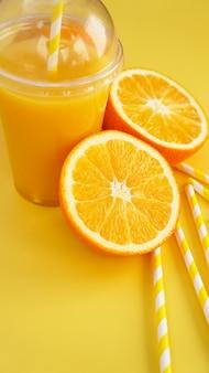 黄色の背景にチューブとファーストフードの閉じたカップのオレンジジュース。オレンジと黄色の紙ストローをスライスして飲み物にしました。縦の写真