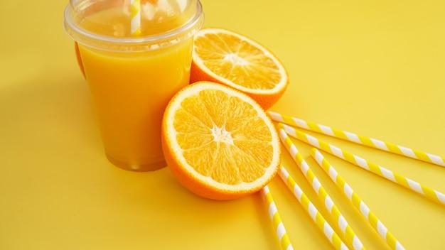 黄色の背景にチューブとファーストフードの閉じたカップのオレンジジュース。飲み物のためにスライスされたオレンジと黄色の紙ストロー