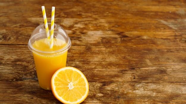 木製のテーブルの上のチューブとファーストフードの閉じたカップのオレンジジュース
