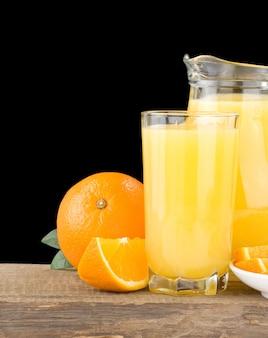 유리와 검은 색 표면에 절연 용기에 오렌지 주스