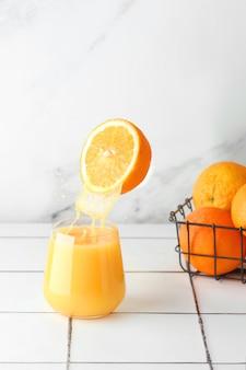 Апельсиновый сок в стеклянном всплеске с плавающей половиной апельсина. концепция летнего напитка левитации. стеклянный сок и апельсин в корзине на плиточном столе.