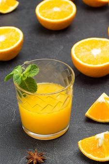 ガラスのオレンジジュース、ミントの小枝。テーブルの上でスライスされたオレンジ。黒の背景。上面図。