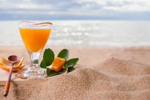 Апельсиновый сок в стекле на песчаном пляже с размытым изображением моря. тропический фрукт .