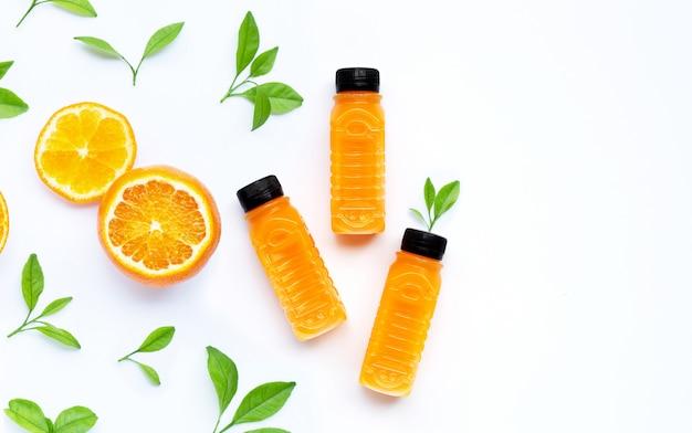Апельсиновый сок в пластиковых бутылках с оранжевыми фруктами на белом