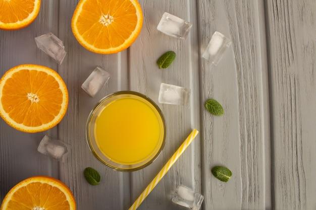 ガラスのオレンジジュースと灰色の木製の背景にオレンジの半分。上面図。コピースペース。