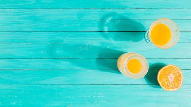 Orange, juice jar and glass on table