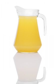 Orange juice in a jug with handle standing on mirror surface isolated on white