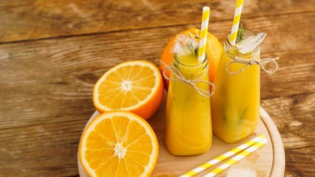 木製トレイにオレンジジュース。スライスしたオレンジと角氷。リゾートでの軽食、暑い夏の日の涼しさ。