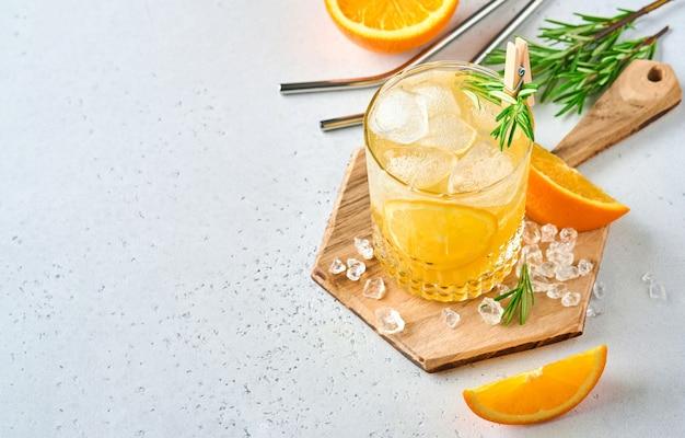 オレンジジュースまたはローズマリーとオレンジ、グラスに氷を入れたオレンジ、ライトグレーのスレート、石またはコンクリートの背景に冷たい夏のレモネード。深い太陽の影とビーチのコンセプト。上面図。