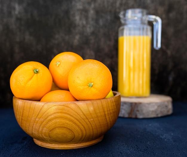Orange juice and pile of oranges in bowl