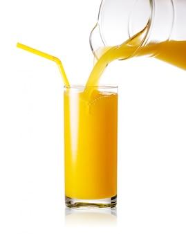 Апельсиновый сок льется из кувшина в стакан с соломой